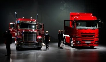 Visitors look at heavy trucks at Daimler exhibition area during preview day at the IAA commercial vehicles trade fair in Hanover.