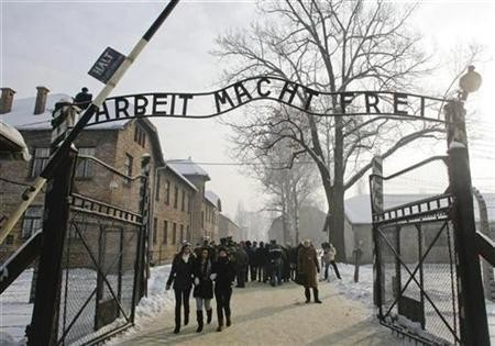 """People walk through the gate, with the words """"Arbeit macht frei"""" (Work sets you free), of the former Nazi death camp of Auschwitz in Oswiecim"""