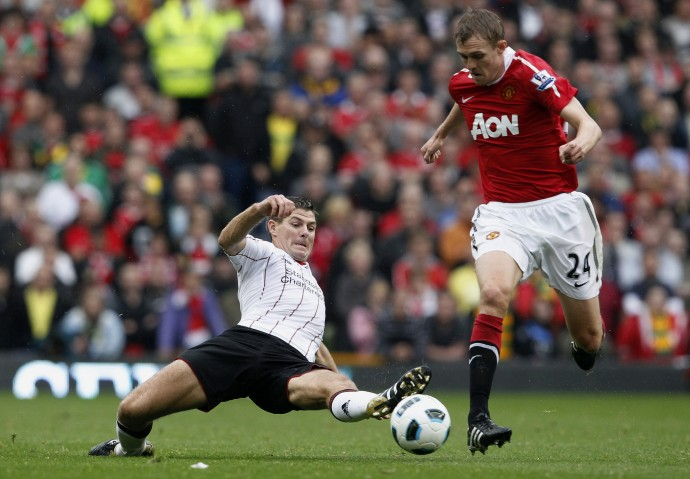 Manchester United's Fletcher is challenged by Liverpool's Gerrard during their English Premier League soccer match at Old Trafford in Manchester.