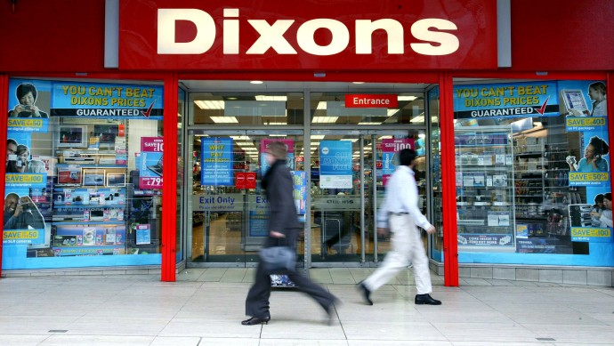 Pedestrians walk past a Dixons electrical retail shop in London