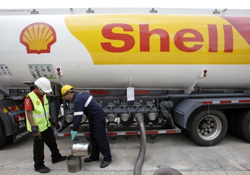 Workers prepare to pump petrol at a Shell station