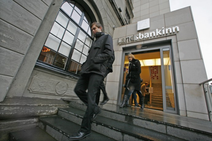 Customers leave the main branch of Landsbankinn Bank in Reykjavik