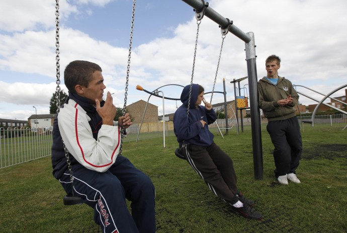 Unemployed youths Chris Gathercole, Samantha Felton and Craig Main sit on and stand by swings in a childrens play area in Aylesbury, southern England