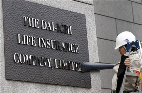 A worker removes masking tape from the new sign board of Dai-ichi Life Insurance Company, Limited at its headquarters in Tokyo April 1, 2010.
