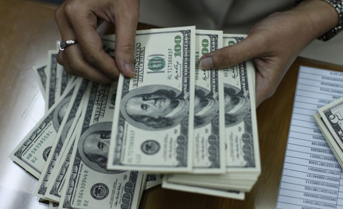 Employee counts U.S. dollar at money changer in Jakarta