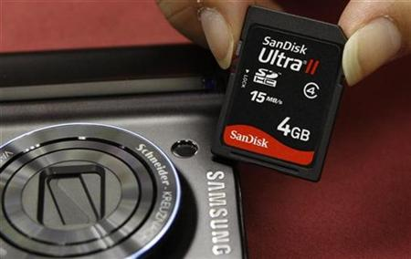 A shopper poses with a SanDisk memory card beside a Samsung camera in Hong Kong.