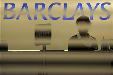 A worker waits for customers in a branch of Barclays bank in London