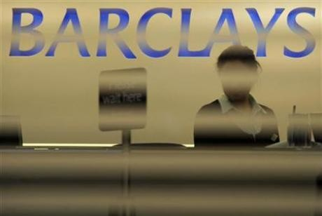 A worker waits for customers in a branch of Barclays bank in London February 16, 2010.