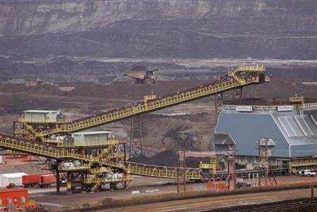 Heavy equipment mines tar sands at Syncrude's Aurora mine in Alberta.