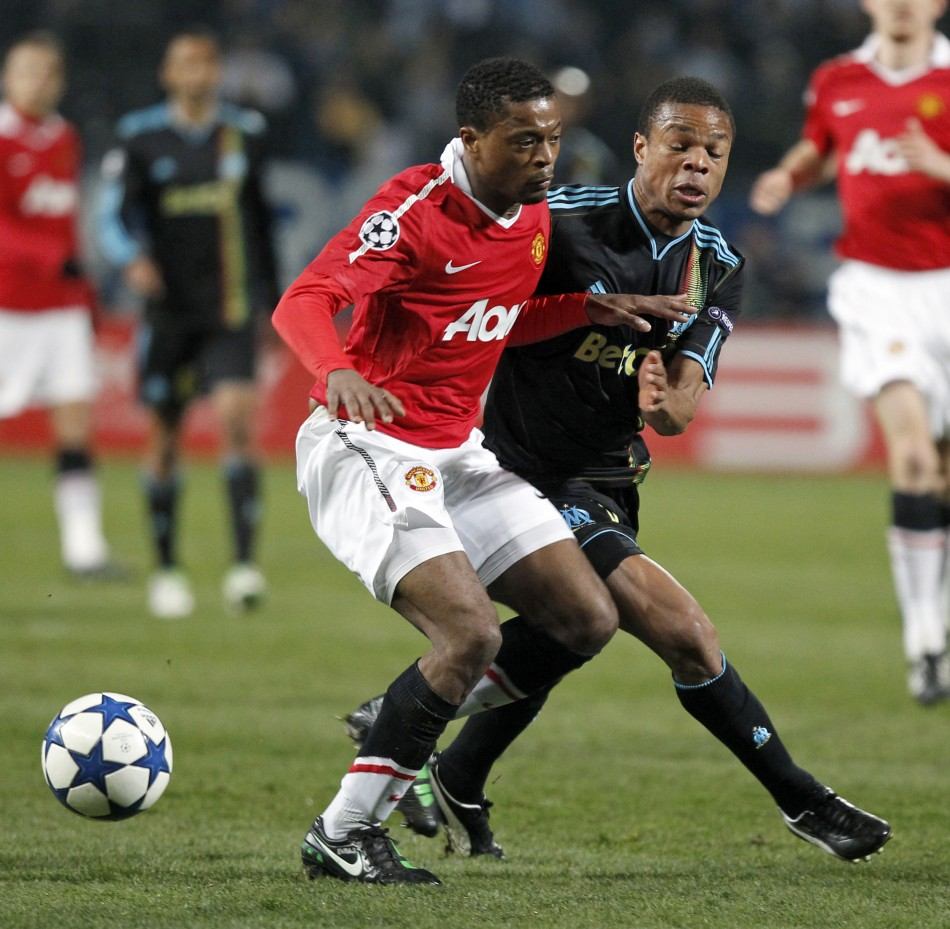 Olympique Marseille's Remy challenges Manchester United's Evra during their Champions League soccer match at the Velodrome stadium in Marseille