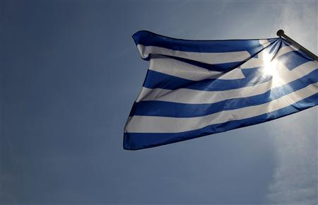 A Greek flag flies in the wind at a park in central Athens