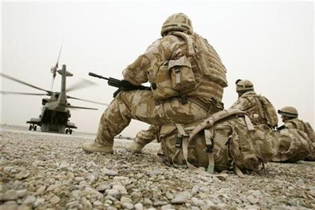 British soldiers wait to be transported to a base in the provincial capital Lashkar Gar in Camp Bastion, Helmand