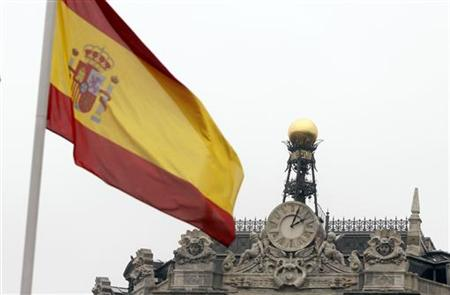 A Spanish flag flutters near the dome of the Bank of Spain in central Madrid