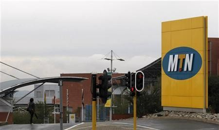 A woman walks past the entrance of the headquarters of South Africa's MTN Group