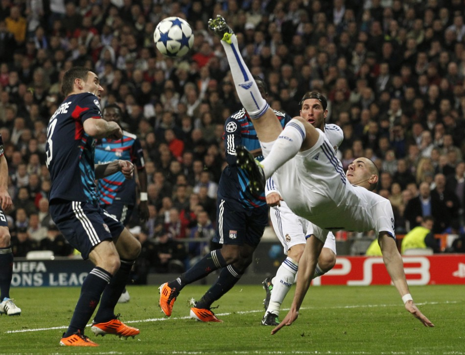 Real Madrid's Benzema tries to kick the ball challenged by Olympique Lyon's Reveillere during their Champions League soccer match in Madrid.