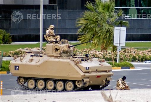 A soldier from the Gulf Cooperation Council (GCC) forces prays in front of his Armour Personnel Carrier in Manama