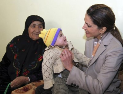 Jordans Queen Rania R holds a baby during a visit