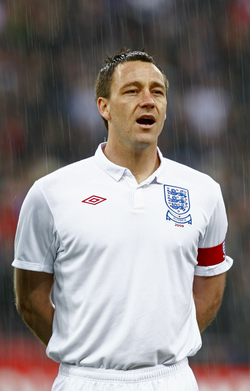England's captain John Terry sings the national anthem in the rain before their international friendly soccer match against Slovakia in London in 2009.