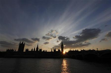 The sun sets behind the Palace of Westminster, in London
