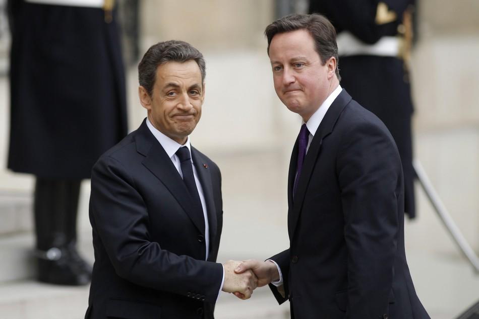 France's President Nicolas Sarkozy (L) greets Britain's Prime Minister David Cameron