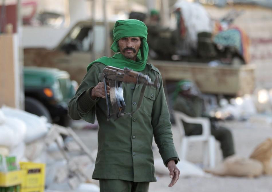 A Libyan soldier loyal to leader Muammar Gaddafi stands in a street strewn with rubble in the city of Misrata, 200 km (124 miles) east of the capital Tripoli March 28,2011.
