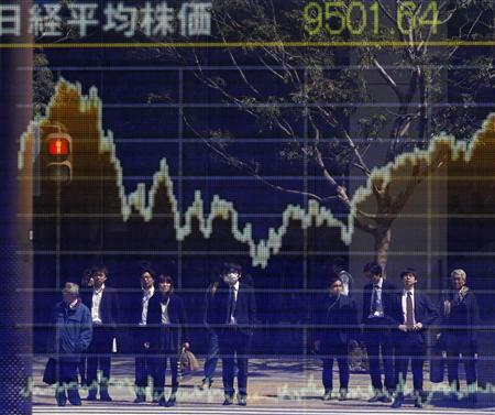 People are reflected on a stock quotation board displaying the Nikkei share average outside a brokerage in Tokyo