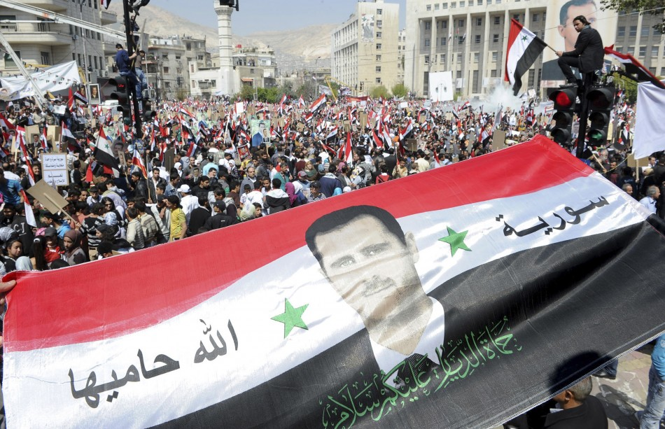 Syrians display a giant national flag with a picture of Syria's President Assad during a pro-government rally at the central bank square in Damascus