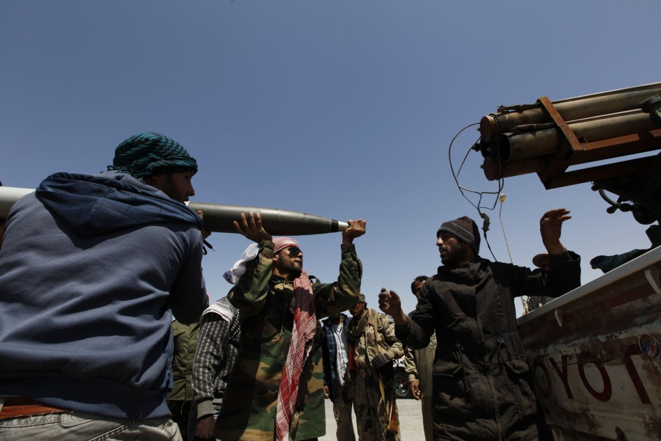 Rebels load a weapon on the road to the frontline in Brega