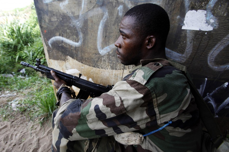 A soldier loyal to Ivory Coast presidential claimant Ouattara holds position along road in Abidjan