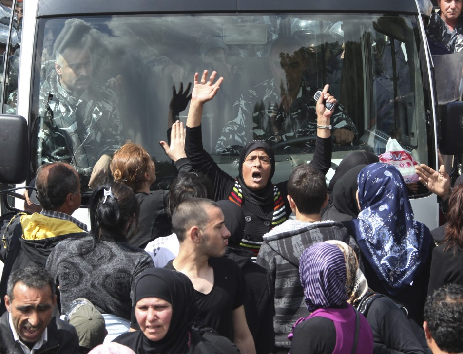 Relatives of inmates in Roumieh prison block the road in front of a policemen bus during a protest near the prison, east of Beirut
