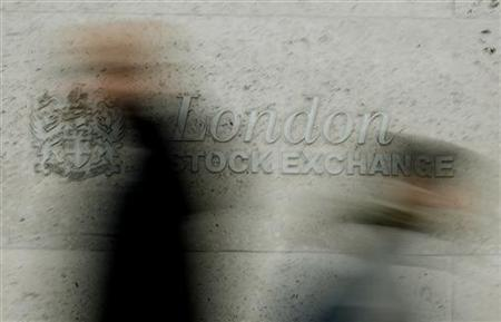 Pedestrians walk past the London Stock Exchange in the City of London
