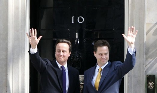 Britain's Prime Minister David Cameron (L) and Deputy Prime Minister Nick Clegg wave on the steps of 10 Downing Street in London May 12, 2010