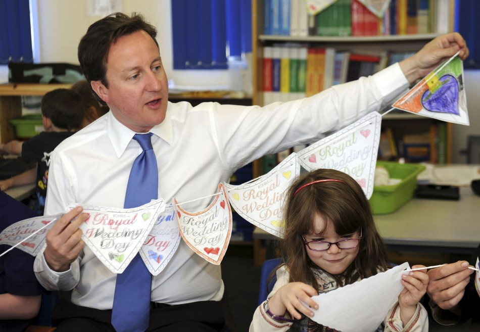Britain's Prime Minister David Cameron helps pupils make royal bunting at the English Martyrs primary school in Manchester, northern England