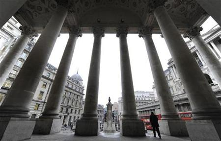 People walk through Royal Exchange with Bank of England seen behind in central London