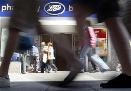 Pedestrians walk past a Boots branch in Leicester, central England