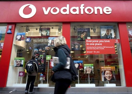 A pedestrian passes a Vodafone store on Oxford Street in central London, November 10, 2009
