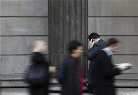 A man uses use mobile phone outside the Bank of England in central London