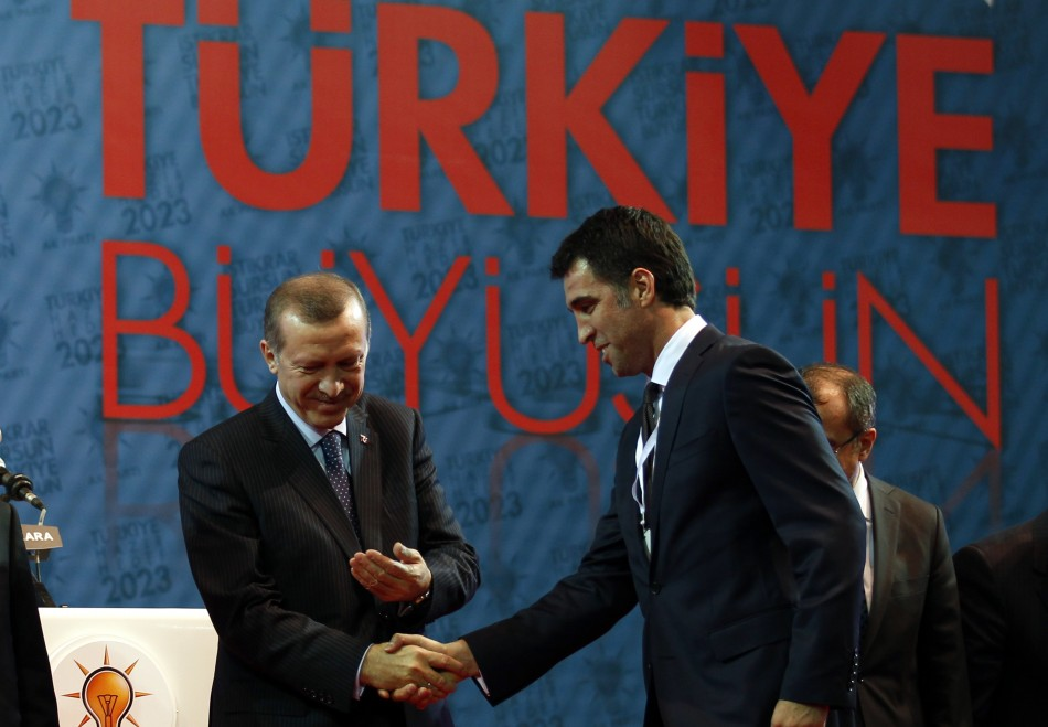 Turkey's PM Erdogan shakes hands with Istanbul candidate Hakan Sukur during a meeting to present his ruling AKP's candidates for the upcoming general elections in Ankara