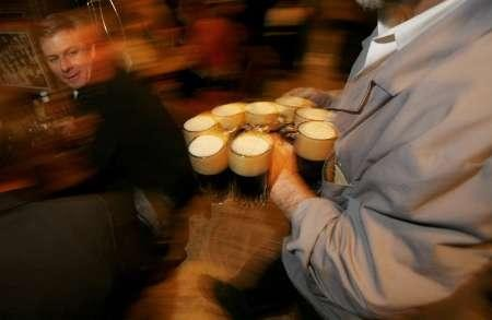 A patron watches as a barman brings a round of beers