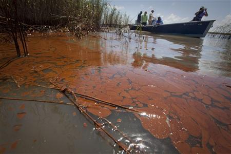 Boat passes through heavily oiled marsh near Pass a Loutre, Louisiana