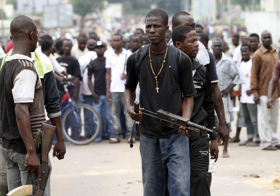 Fighters of a militia supporting ex-president Gbagbo walk with their weapons during a symbolic disarmament ceremony for the pro-Gbagbo militia group in Yopougon
