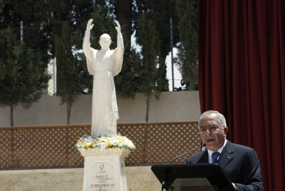 Palestinian PM Fayyad speaks in front of a statue of Pope John Paul II during a ceremony in Bethlehem