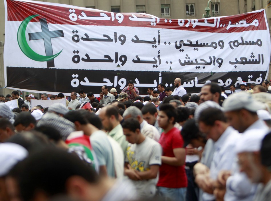People take part in Friday prayers during a protest at Tahrir Square in Cairo