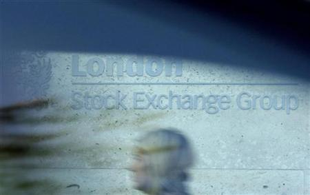 A woman is seen through a car window as she walks past the London Stock Exchange