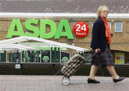 A shopper walks past an Asda superstore in south London