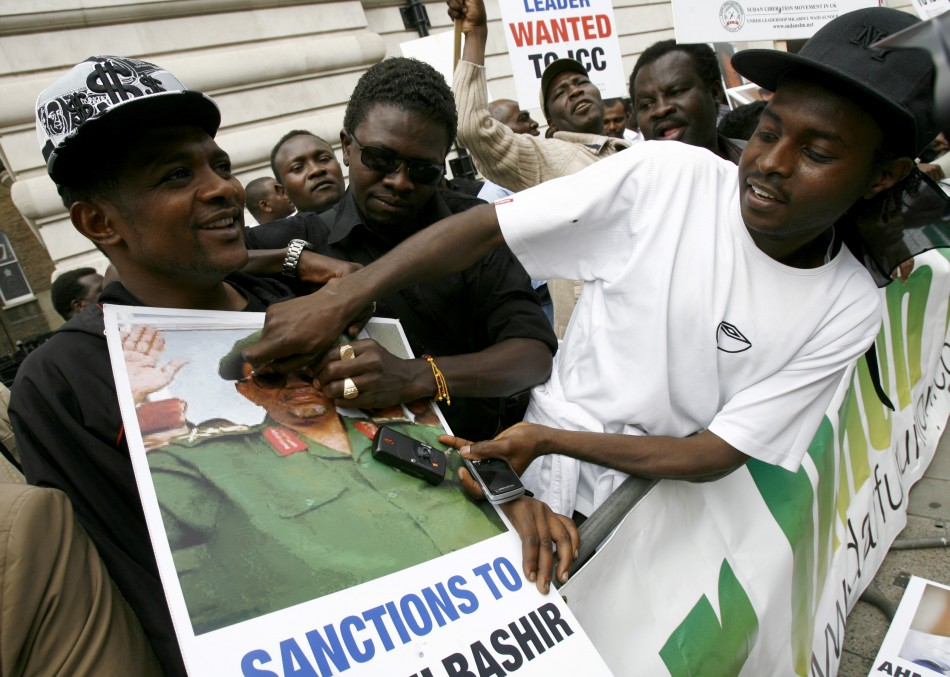 A protester defaces a picture of Sudanese President Bachir outside the Sudanese Embassy in London