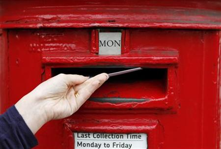 A woman posts a letter into a post box in south London
