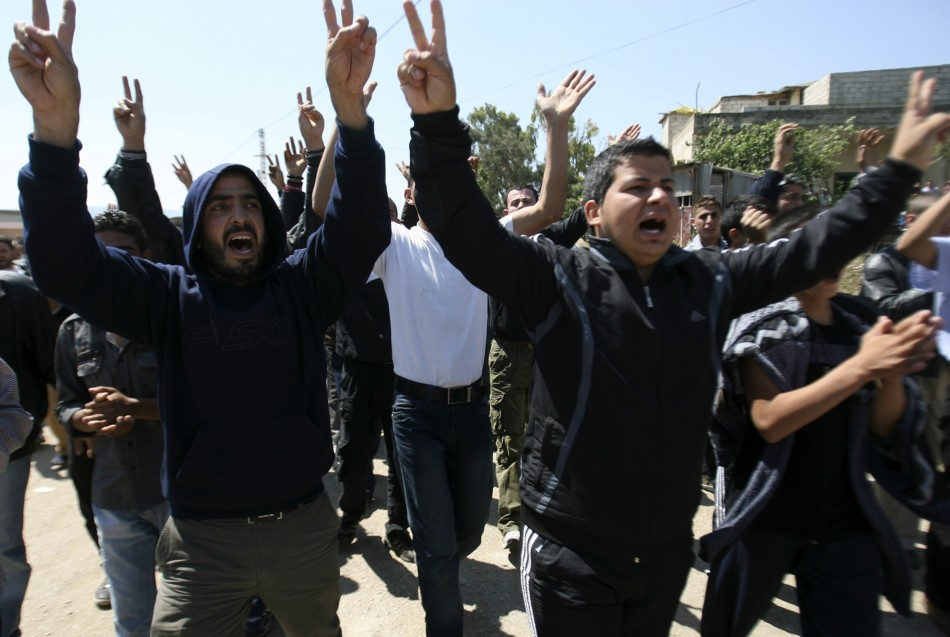 Syrian men chant slogans against their President Bashar al-Assad after arriving in Wadi Khaled in northern Lebanon